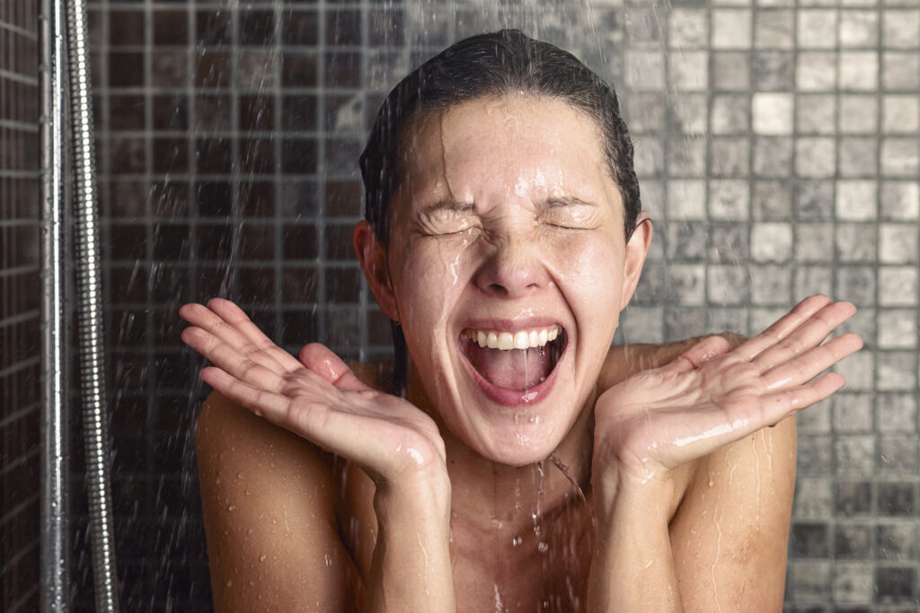 Young woman reacting in shock to hot or cold shower water